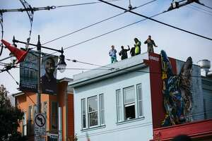 Participants dance on the roofs during the Bay to Breakers annual race in San Francisco, Calif., Sunday, May 20, 2018.