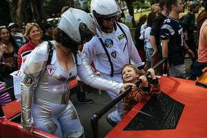 Anya Louisa and Dan Tarcy help Cosima Felten, 4, carry their Tesla float during the Bay to Breakers annual race in San Francisco, Calif., Sunday, May 20, 2018.