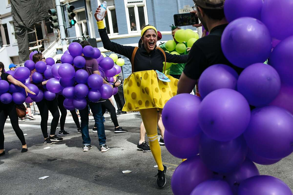 Nazanine Bain, in the cheese costume, dances along with the participants dress as grapes during the Bay to Breakers annual race in San Francisco, Calif., Sunday, May 20, 2018.
