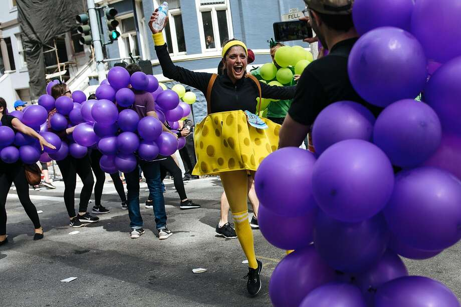 Nazanine Bain, in the cheese costume, dances along with the participants dress as grapes during the Bay to Breakers annual race in San Francisco, Calif., Sunday, May 20, 2018. Photo: Mason Trinca, Special To The Chronicle