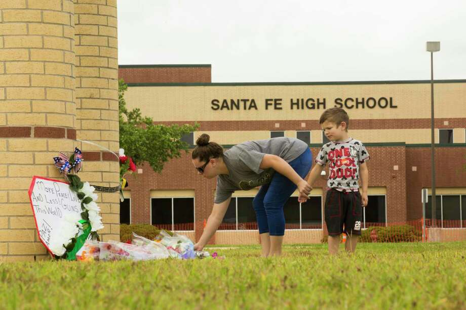 A woman puts down flowers on front of the Santa Fe High School where two days ago ten people were shot. Sunday, May 20, 2018, in Santa Fe. Photo: Marie D. De Jesus, Houston Chronicle / © 2018 Houston Chronicle