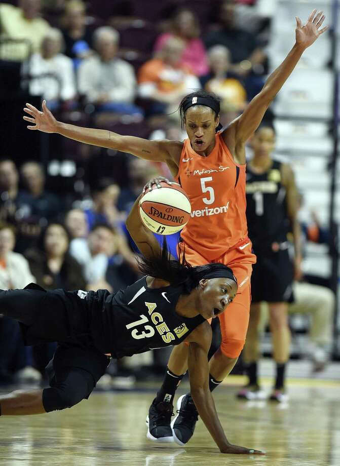 Las Vegas Aces guard Raigyne Louis (13) falls to the floor as the Sun's Jasmine Thomas defends in the second half Sunday in Uncasville. Photo: Sean D. Elliot / The Day Via AP / 2018 The Day Publishing Company