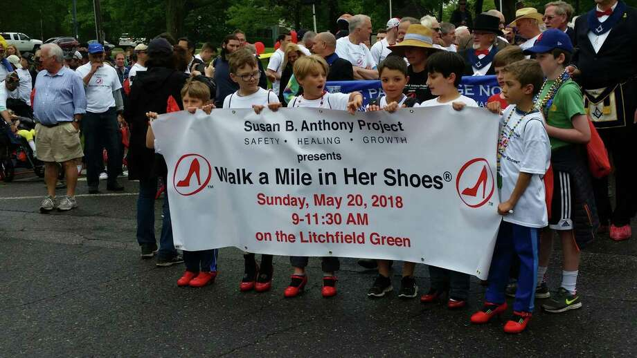 A group of young participants carried a banner in the first Walk a Mile In Her Shoes at the Litchfield Town Green. Photo: N.F. Ambery / Hearst Connecticut Media