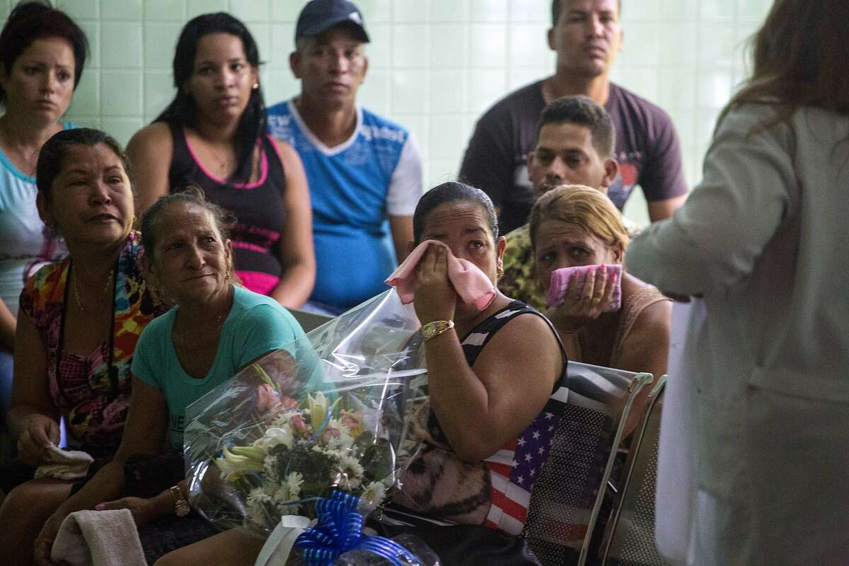 Grieving relatives of passengers who perished in Cuba's worst aviation disaster wait at the morgue for the identification of the bodies in Havana, Cuba, Sunday, May 20, 2018. Officials say 110 people died when a charter passenger jet hired by Cuba's state-run airline, Cubana de Aviacion, crashed Friday in the rural outskirts of Havana. (AP Photo/Desmond Boylan)