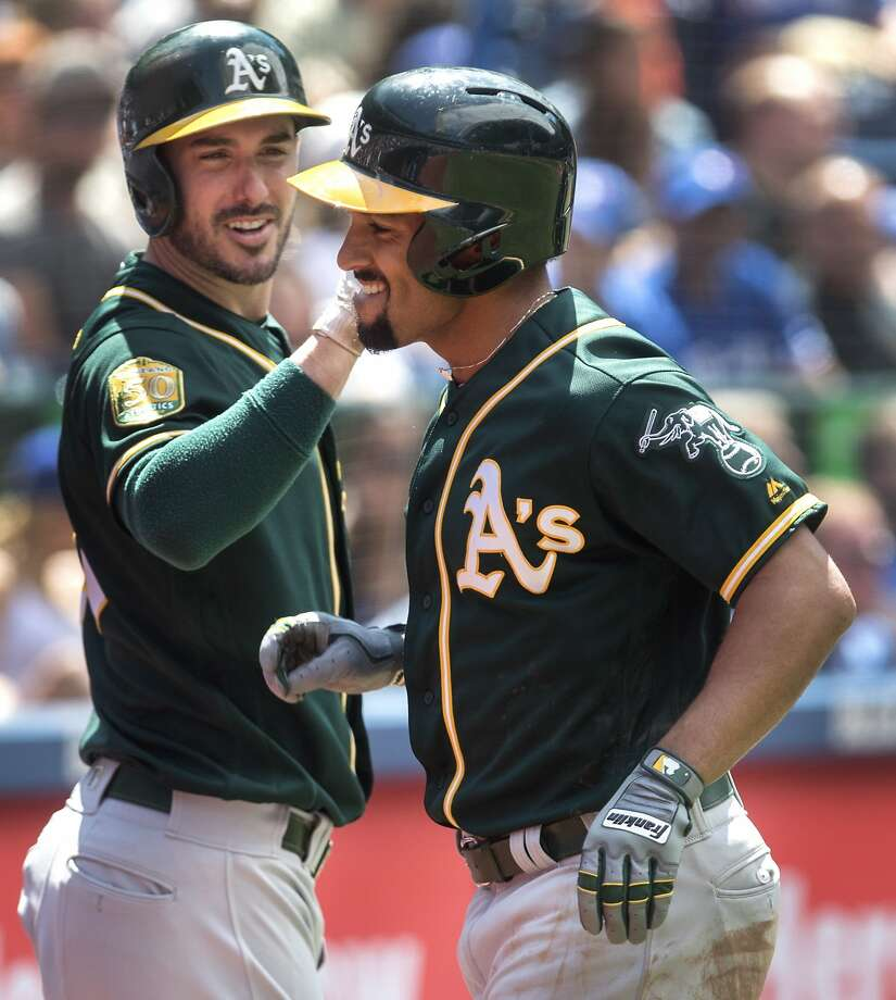 Oakland Athletics' Marcus Semien, right, comes in to score after hitting a two-run home run during fifth-inning baseball game action against the Toronto Blue Jays in Toronto, Sunday, May 20, 2018. Photo: Fred Thornhill / Associated Press