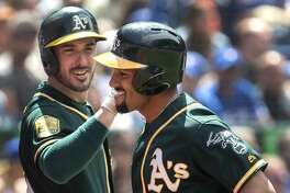 Oakland Athletics' Marcus Semien, right, comes in to score after hitting a two-run home run during fifth-inning baseball game action against the Toronto Blue Jays in Toronto, Sunday, May 20, 2018. (Fred Thornhill/The Canadian Press via AP)
