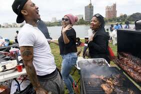 Michael Woods dances with his sister Clarice Brown (center) and their mother, Michelle Beasley, while tending to his grill.
