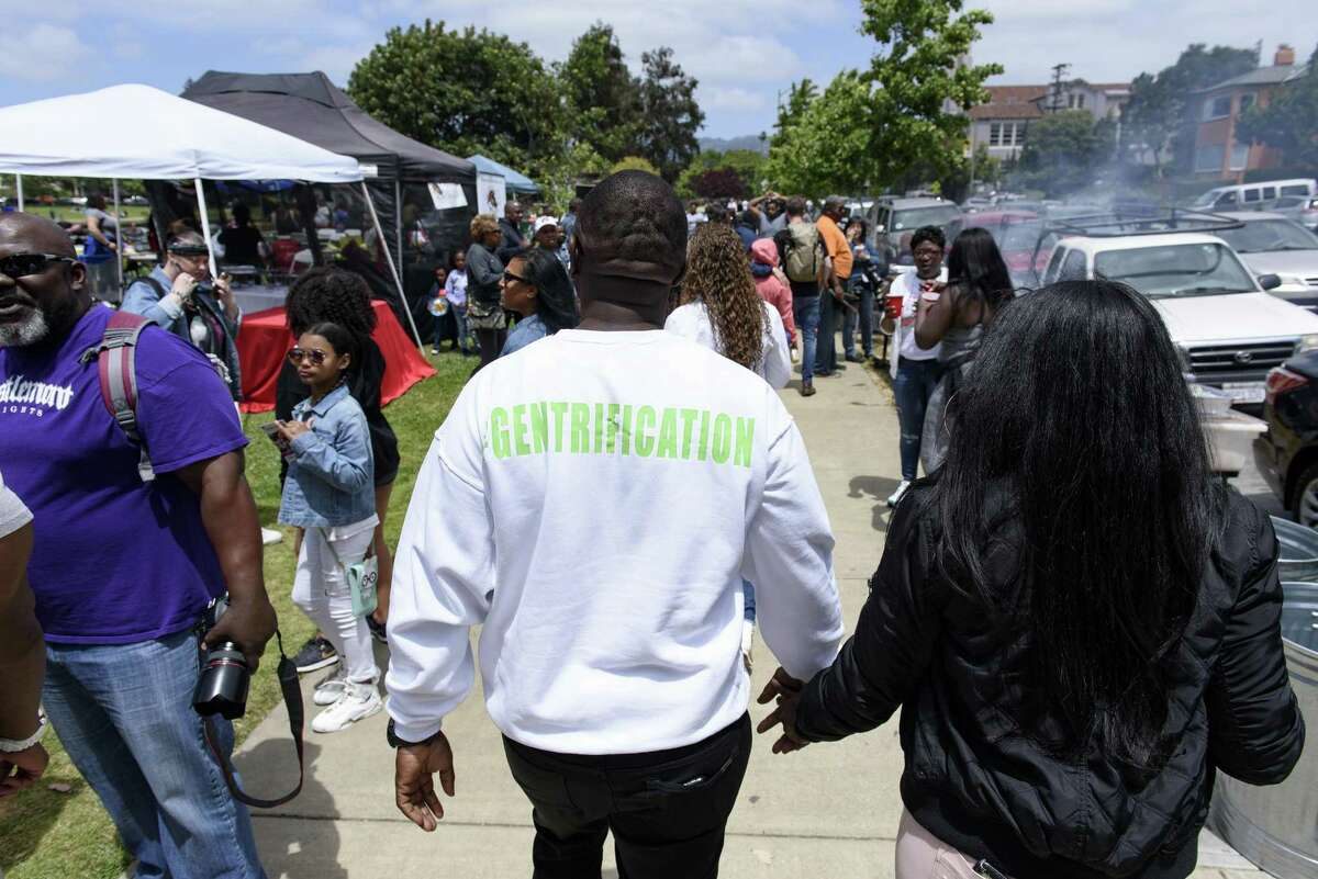 """Aloysius McMahan of Oakland wears a sweatshirt with the """"#Gentrification"""" on the back during the barbecue at Lake Merritt."""