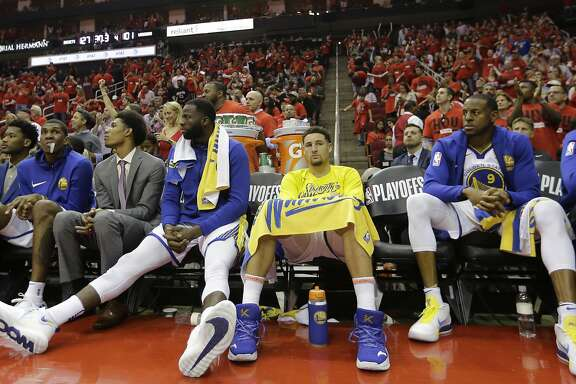 Golden State Warriors players including forward Draymond Green, center with legs extended, guard Klay Thompson, center, and Andre Iguodala (9) sit on the bench during the final moments of the second half in Game 2 of the NBA basketball Western Conference Finals against the Houston Rockets, Wednesday, May 16, 2018, in Houston. (AP Photo/David J. Phillip)