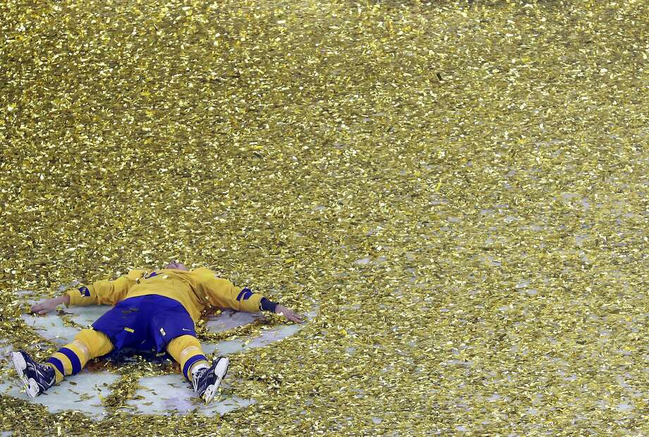 Sweden's Hampus Lindholm makes a snow angel in the ice among the confetti after winning the Ice Hockey World Championships final match between Sweden and Switzerland at the Royal arena in Copenhagen, Denmark, Sunday, May 20, 2018. (AP Photo/Petr David Josek) Photo: Petr David Josek / Associated Press