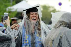 As rain begins to fall, graduates put on rain ponchos during the University at Albany undergraduate commencement ceremony on Sunday, May 20, 2018, in Albany, N.Y.   (Paul Buckowski/Times Union)
