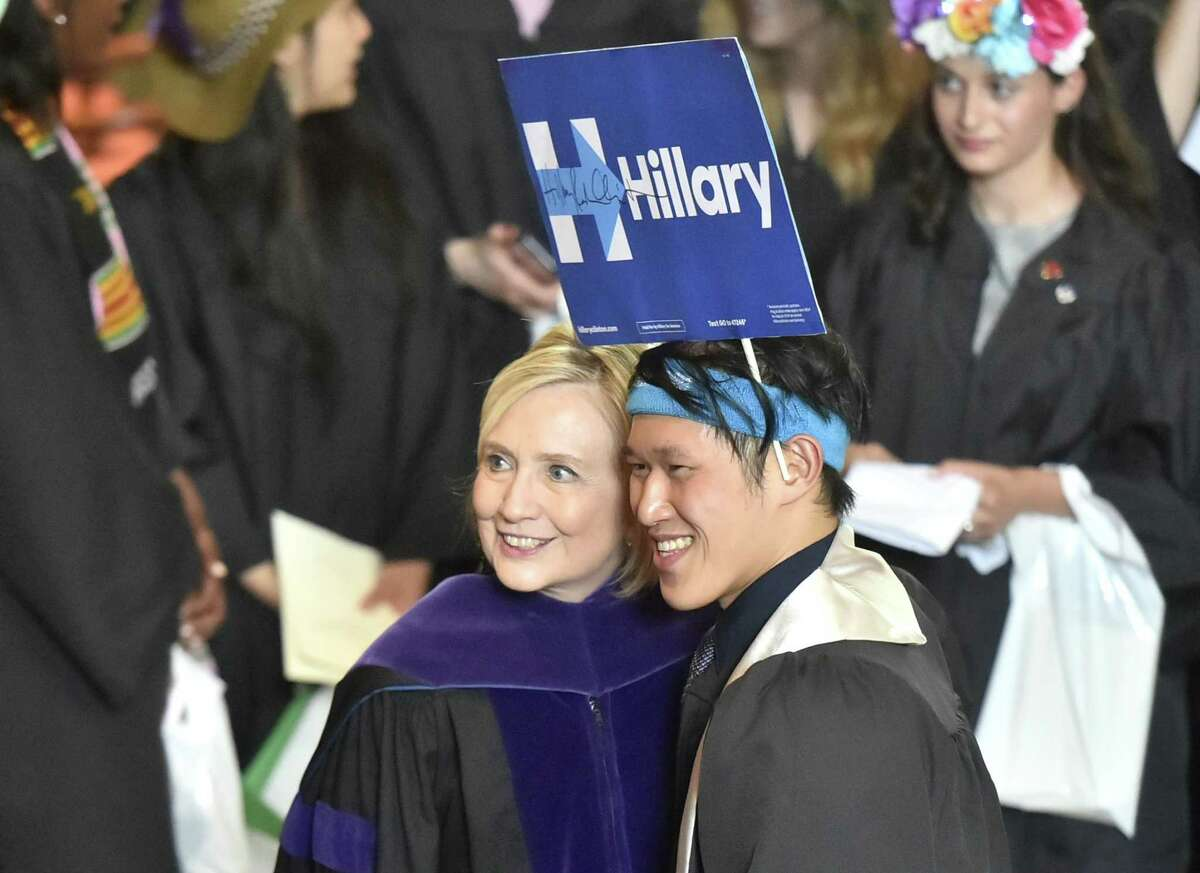 New Haven, Connecticut - Sunday, May 20, 2018: After autographing a campaign poster, former Secretary of State and former Democratic Presidential candidate Hillary Clinton poses with Yale senior and political science major Ryan Liu of California after her Class Day address Sunday afternoon at Yale University's Woolsey Hall in New Haven to the Yale College class of 2018. As a tradition, Yale students and faculty wear humorous and playful hats during Class Day Exercises.