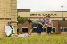 A woman puts down flowers on front of the Santa Fe High School where two days ago ten people were shot. Sunday, May 20, 2018, in Santa Fe. ( Marie D. De Jesus / Houston Chronicle )