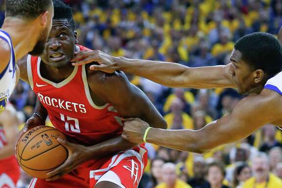 Golden State Warriors forward Kevon Looney (5) reacheas in to grab Houston Rockets center Clint Capela (15) during the first half of Game 3 of the Western Conference Finals at Oracle Arena Sunday, May 20, 2018 in Oakland.