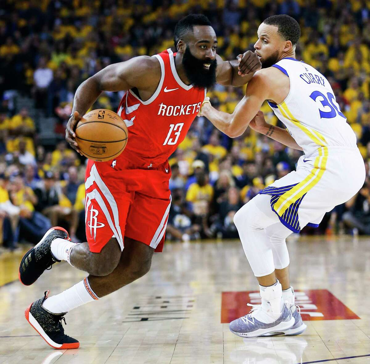 Houston Rockets guard James Harden (13) drives past Golden State Warriors guard Stephen Curry (30) during the first half of Game 3 of the Western Conference Finals at Oracle Arena Sunday, May 20, 2018 in Oakland.