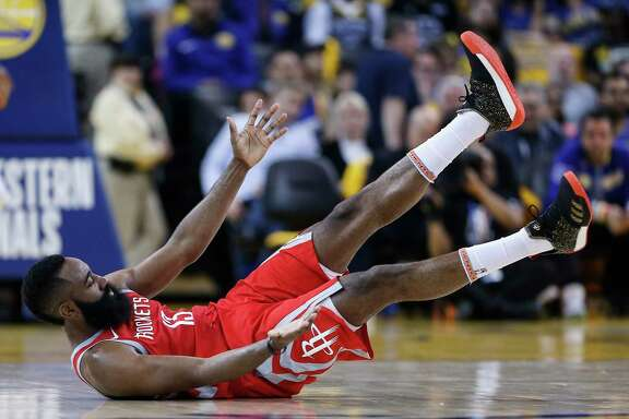 Houston Rockets guard James Harden (13) falls to the court after colliding with Golden State Warriors forward Draymond Green (23) during the first half of Game 3 of the Western Conference Finals at Oracle Arena Sunday, May 20, 2018 in Oakland.