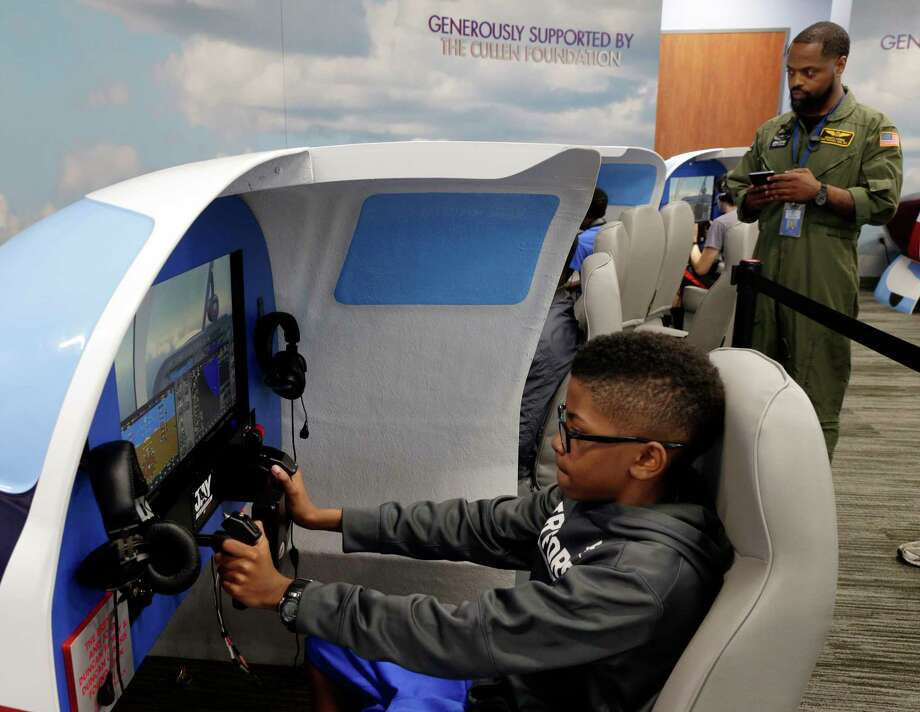 Ethan White, age 11, takes over the controls on one of two official simulators as Kenneth Morris, director of education at the museum, oversees the simulation as they take part in the Lindbergh Challenge at the Lone Star Flight Museum in Houston, TX, Sunday, May 20, 2018.  Local students, Civil Air Patrol and the Boy Scouts take shifts in Red Bird simulators to replicate Lindbergh's 33 1/2 hour May 20, 1927 flight across the Atlantic ocean. (Michael Wyke / For the  Chronicle) Photo: Michael Wyke, For The Chronicle / © 2018 Houston Chronicle