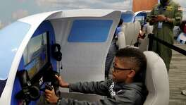Ethan White, age 11, takes over the controls on one of two official simulators as Kenneth Morris, director of education at the museum, oversees the simulation as they take part in the Lindbergh Challenge at the Lone Star Flight Museum in Houston, TX, Sunday, May 20, 2018.  Local students, Civil Air Patrol and the Boy Scouts take shifts in Red Bird simulators to replicate Lindbergh's 33 1/2 hour May 20, 1927 flight across the Atlantic ocean. (Michael Wyke / For the  Chronicle)