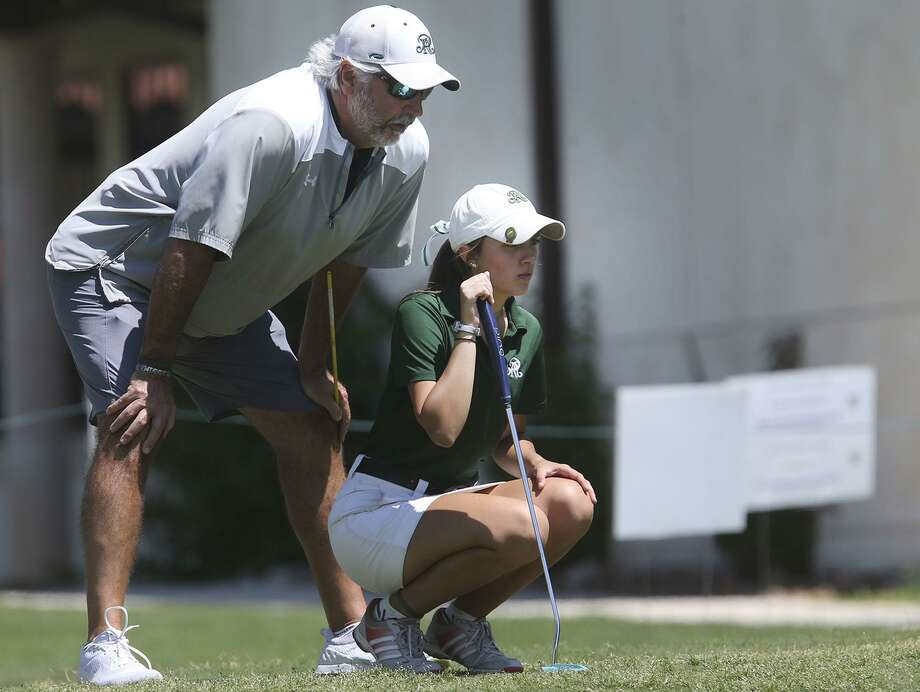 Reagan coach Brent McCuiston (left) eyes a putt with junior Kinsey Ray during the Region IV-6A girls golf event in April. Photo: John Davenport / San Antonio Express-News / ©John Davenport/San Antonio Express-News