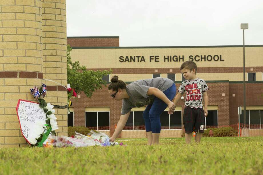 A woman puts down flowers on front of Santa Fe High School, where 10 people were killed and 13 injured in a mass shooting. Photo: Marie D. De Jesus, Houston Chronicle / Houston Chronicle / © 2018 Houston Chronicle