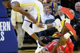 Houston Rockets guard James Harden (13) falls to the floor as he is defended by Golden State Warriors forward Andre Iguodala (9) during the second half of Game 3 of the Western Conference Finals at Oracle Arena Sunday, May 20, 2018 in Oakland.