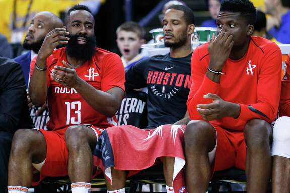 Houston Rockets James Harden (13), Trevor Ariza (1) and  Clint Capela (15) sit on the bench during the second half of Game 3 of the Western Conference Finals against the Golden State Warriors at Oracle Arena Sunday, May 20, 2018 in Oakalnd.