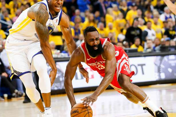 Houston Rockets' James Harden falls after Golden State Warriors' Andre Iguodala tried to pull the ball away from him in the fourth quarter during game 3 of the Western Conference Finals between the Golden State Warriors and the Houston Rockets at Oracle Arena on Sunday, May 20, 2018 in Oakland, Calif.