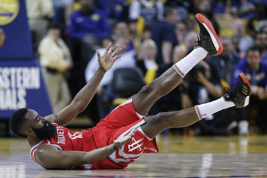 Rockets guard James Harden falls to the court after colliding with Golden State Warriors forward Draymond Green during the first half of Game 3 Sunday night. Photo: Michael Ciaglo, Houston Chronicle / Houston Chronicle / Michael Ciaglo