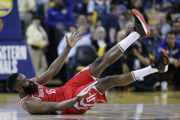Rockets guard James Harden falls to the court after colliding with Golden State Warriors forward Draymond Green during the first half of Game 3 Sunday night.