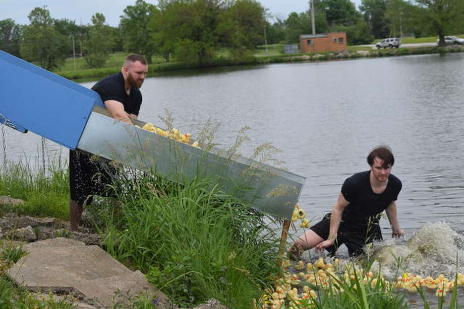 Andy and Dan Selway release the ducks Sunday at the annual Duck Race for Lifeline at Nichols Park. The event raises money to buy Lifeline units and to provide service to those unable to afford it. Photo:       Audrey Clayton | Journal-Courier