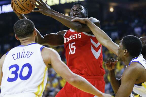 Rockets center Clint Capela (15) is fouled by Warriors forward Kevon Looney (5) during the first half of Game 3. Capela muscled his way to 13 points anyway.