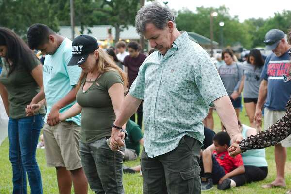 Jacob Balvantin, Lisa Dale and Tom Dale hold hands and bow their heads in pryaer during a vigil hosted by Moms of Galveston County Sunday, May 20 at Walter Hall Park in League City following the shooting tragedy at Santa Fe High School.