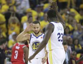 Golden State Warriors' Stephen Curry and Draymond Green high five in the third quarter during game 3 of the Western Conference Finals between the Golden State Warriors and the Houston Rockets at Oracle Arena on Sunday, May 20, 2018 in Oakland, Calif.