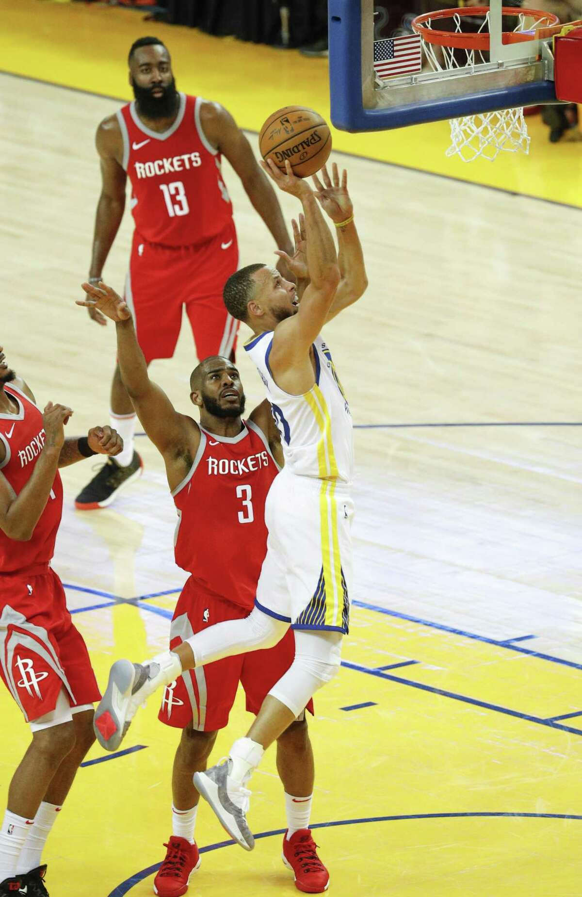 Golden State Warriors' Stephen Curry goes in for a layup over Houston Rockets' Chris Paul in the second quarter during game 3 of the Western Conference Finals between the Golden State Warriors and the Houston Rockets at Oracle Arena on Sunday, May 20, 2018 in Oakland, Calif.