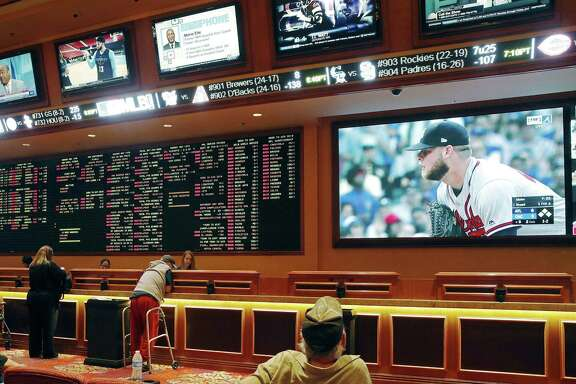 In this Monday, May 14, 2018 file photo, people make bets in the sports book area of the South Point Hotel and Casino in Las Vegas. Those who deal with compulsive gambling are worried that a rapid expansion of sports betting in the U.S. could cause more people to develop gambling problems. The U.S. Supreme Court on Monday cleared the way for states to legalize sports betting.