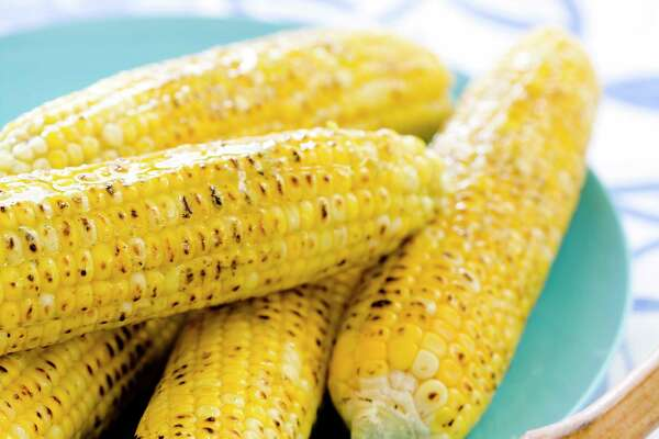 """This undated photo provided by America's Test Kitchen in May 2018 shows grilled corn on the cob in Brookline, Mass. This recipe appears in """"The Complete Cook's Country TV Cookbook, 2017."""" (Joe Keller/America's Test Kitchen via AP)"""