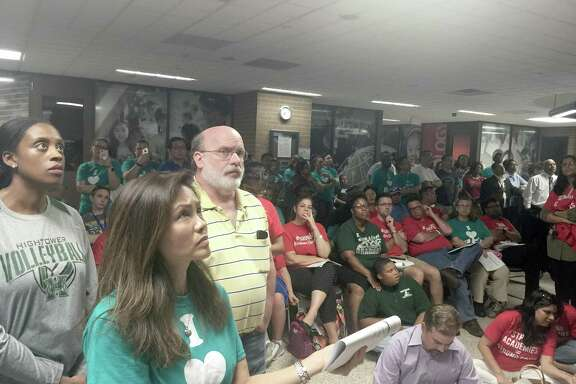 Hundreds of anxious parents and residents watch as Fort Bend ISD trustees discuss long-term plans for the district's schools and facilities in an overflow area outside the full-to-capacity board room. Many more were turned away at the door by police after the lobby area became too full to navigate safety on Monday, May 14.