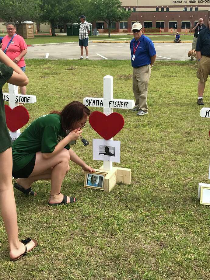 Santa Fe students lay flowers and photos at the foot of 10 white crosses displayed in front of the high school, for each of the victims of Friday's shooting on Monday, May 21, 2018.  Photo: Nick Powell