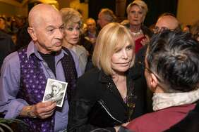"Alex Gildzen (left) stands next to Kim Novak holding a signed photo she sent him 60 years ago after he sent a ""get well"" card when she was in the hospital."