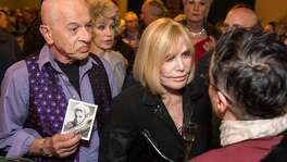 "Kim Novak surrounded by fans and guests at an event in her honor ""A Tribute to living Legend Kim Novak"" at the Castro Theater on Sunday, May 20, 2018. San Francisco Calif. Alex Gildzen standing next to Novak holds signed photograph of her, which she sent to him about 60 years ago. When Alex Gildzen sent Novak a ""get well"" card when she was in the hospital, she responded by sending him this signed photograph."
