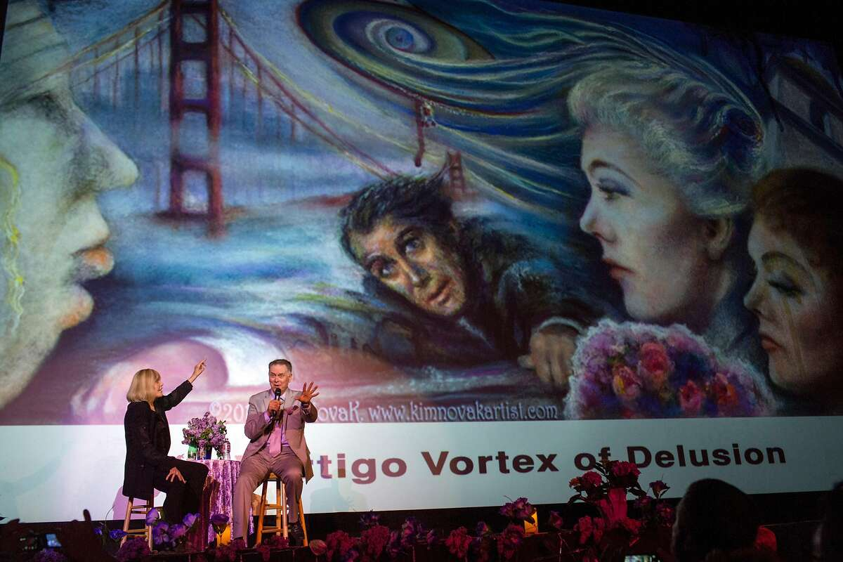 """The host, Eddie Muller interviews Kim Novak on stage during an event in her honor """"A Tribute to Living Legend Kim Novak"""" at the Castro Theater. The image on the screen behind them is one of Novak's paintings depicting the film Vertigo. On Sunday, May 20, 2018. San Francisco Calif."""