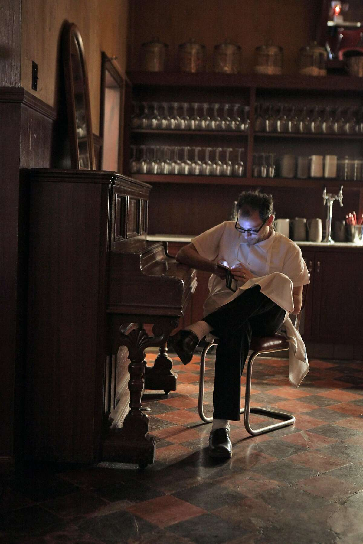 Head Chef Josh Even checks his phone on a break near the old piano at Tosca on Monday. San Francisco's legendary Tosca is set to reopen this week under new ownership, featuring a restaurant as well as the bar. April Bloomfield of Spotted Pig helms the dining, and Co-owner Ken Friedman hopes the changes will bring back regulars and a new crowd. The San Francisco, Calif., mainstay is seen here on Monday, October 7, 2013.