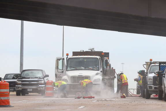 Construction workers repair damage to two left westbound lanes of I-610 North, near the Hardy Toll Road, after a truck lost concrete blocks Monday, May 21, 2018, in Houston.
