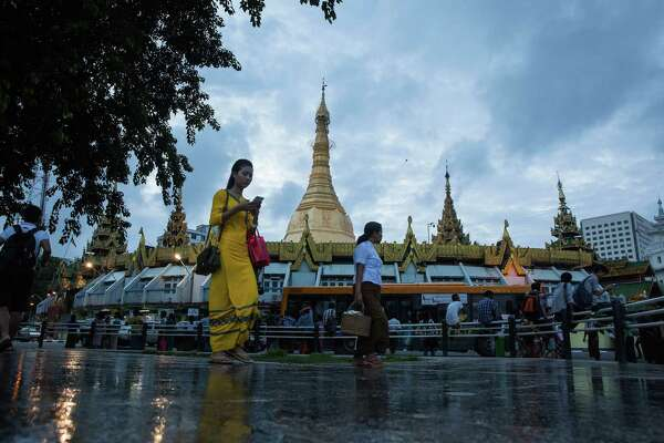 A woman uses a smartphone while walking past the Sule Pagoda stupa at Maha Bandula Park in Yangon, Myanmar, on June 15, 2017. In 2015,