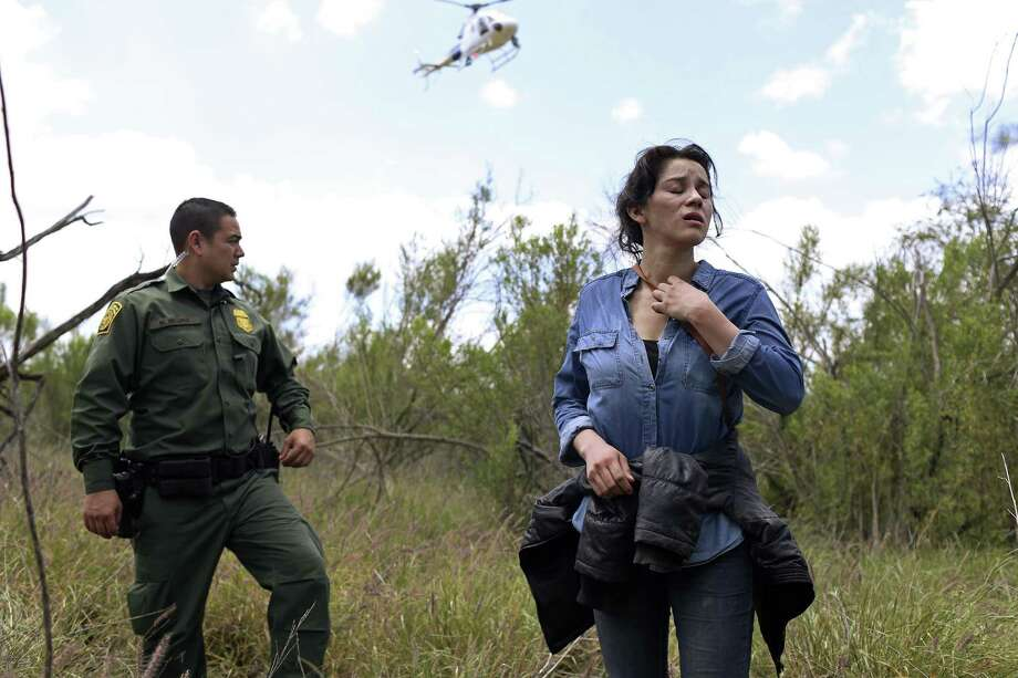 U.S. Border Patrol agent Marcelino Medina detains Veronica Reyes, 26, of Veracruz, Mexico, near the Anzalduas International Bridge in Mission, Texas, Thursday, May 10, 2018. Reyes was with a group of five immigrants attempting to enter the U.S. illegally. The rest were able to cross back into Mexico and escape detention. Photo: JERRY LARA / San Antonio Express-News / San Antonio Express-News