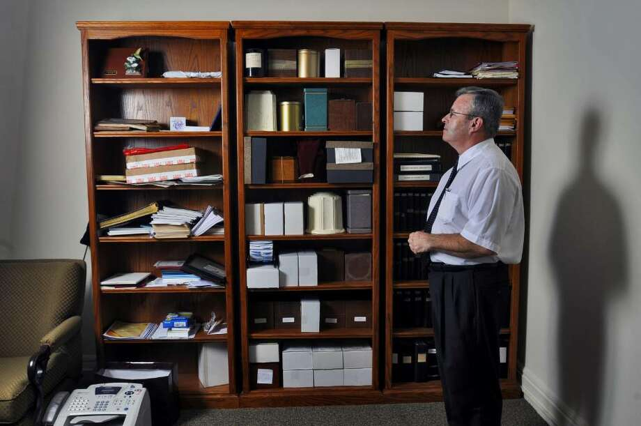 The center shelf at the William J. Burke & Sons/Bussing & Cunniff Funeral Homes in Saratoga Springs contains 38 containers of unclaimed cremated remains, said funeral director Mark Phillips, shown here.  (Philip Kamrass / Times Union Photo: PHILIP KAMRASS