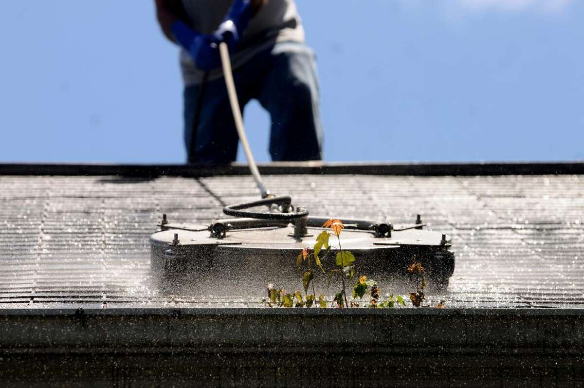 Mike Bursiewicz of Bright Homes Enterprises shampoos a customer's roof in Ballston Spa. The roof had lichens and moss on it, and small maple trees growing in the gutters. (Cindy Schultz / Times Union)