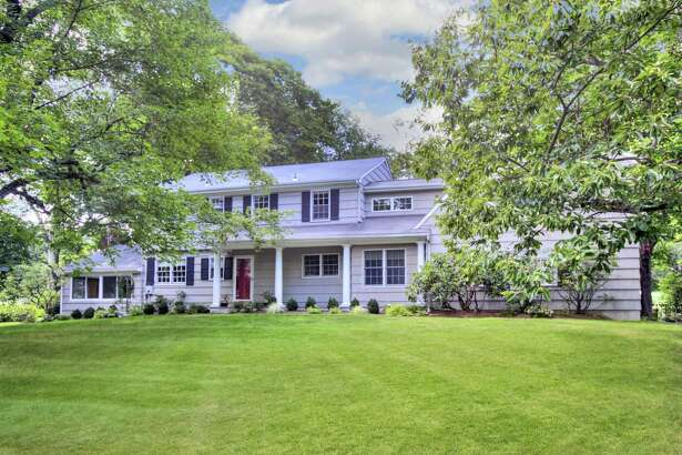 The gray colonial house at 15 Rockyfield Road has a covered front porch, 13 rooms, and 3,661 square feet of living space.
