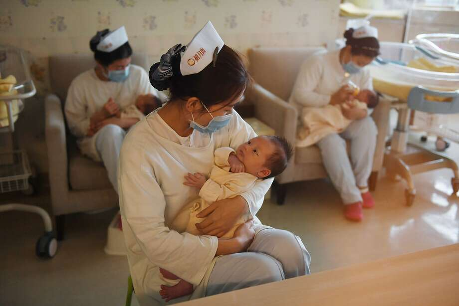 """This photo taken on December 13, 2016 shows nurses holding babies at the Xiyuege Centre,  or """"Lucky Month Home"""", in Beijing.   Since the late 70s, strict measures in the worlds most populous country restricted most couples to only a single offspring with a system of fines for violators and even forced abortions. But concerns over an ageing population, gender imbalances and a shrinking workforce pushed authorities to end the restriction, allowing all couples a second child from January 1. / AFP / Greg Baker / TO GO WITH China population politics children social, FOCUS by Becky DAVIS        (Photo credit should read GREG BAKER/AFP/Getty Images) Photo: GREG BAKER, AFP/Getty Images"""