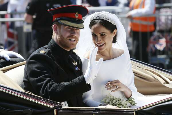 Britain's Prince Harry and Meghan Markle ride in an open-topped carriage after their wedding ceremony at St. George's Chapel in Windsor Castle in Windsor, near London, England, Saturday, May 19, 2018. (Aaron Chown/pool photo via AP)